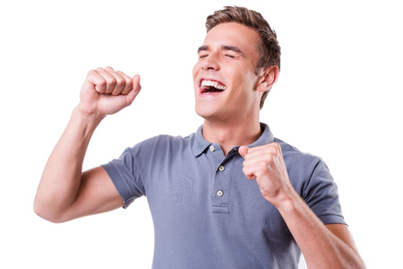 closed fist: I am so happy! Happy young man keeping eyes closed and gesturing while standing isolated on white background Stock Photo