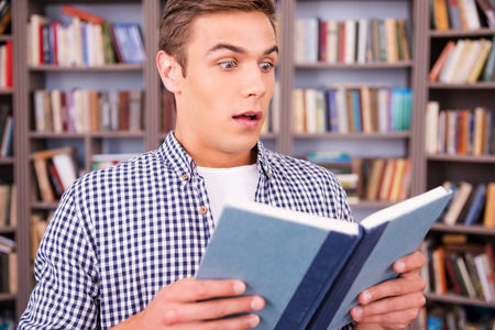 Reading an exciting book. Surprised young man reading book and keeping mouth open while standing in library photo
