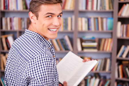 looking over shoulder: Happy bookworm. Rear view of happy young man holding book and looking over shoulder while standing against bookshelf