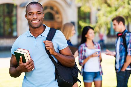 estudiante: Disfrutar de la vida universitaria. Apuesto joven hombre africano celebraci�n de libros y sonr�e mientras est� de pie en contra de la universidad con sus amigos en el chat en el fondo