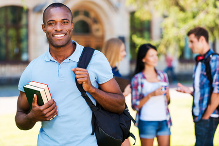 Enjoying university life. Handsome young African man holding books and smiling while standing against university with his friends chatting in the background  Standard-Bild