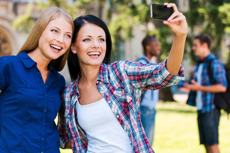 happy moment: Catching a happy moment. Two beautiful young women making selfie while standing close to each other with two men talking in the background