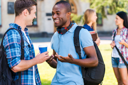college building: Can you believe it? Two young men talking to each other and smiling while two women standing in the background