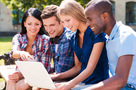 Surfing the net together. Four happy young people looking at\ laptop and smiling while sitting outdoors together