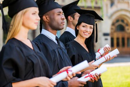 birrete de graduacion: Graduado feliz. Cuatro graduados universitarios de pie en una fila y la celebraci�n de sus diplomas, mientras que una mujer mirando a la c�mara y sonriendo