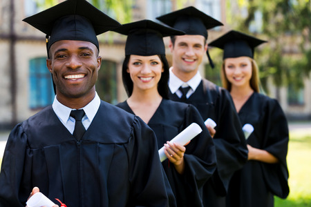 college life: Happy college graduates. Four college graduates standing in a row and smiling Stock Photo
