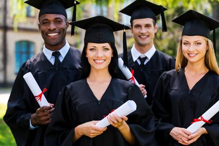 graduacion de universidad: Sentirse seguro en su futuro. Cuatro graduados universitarios en vestidos de graduación de pie cerca uno del otro y sonriendo Foto de archivo