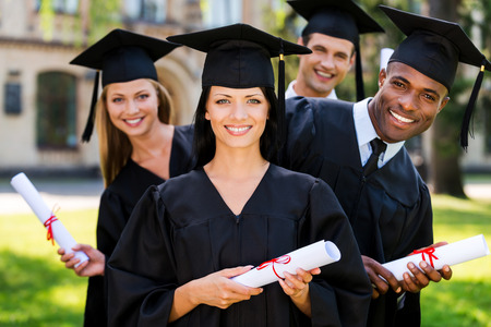 headwear: Finally graduated! Four college graduates holding diplomas and smiling while standing in a row  Stock Photo
