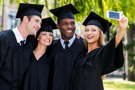 egresado: La captura de un momento feliz. Cuatro graduados universitarios en vestidos de graduaci�n de pie cerca uno del otro y haciendo selfie Foto de archivo