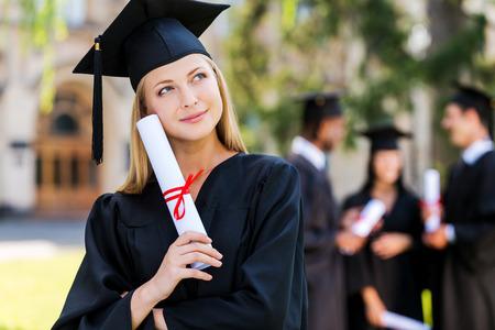 graduacion de universidad: El sue�o de un futuro brillante. Mujer joven pensativa en vestidos de graduaci�n que sostienen el diploma y mirando a otro lado mientras sus amigos de pie en el fondo