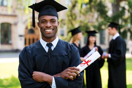 toga graduacion: Graduado feliz. Hombre africano feliz en vestidos de graduación celebración diploma y sonriendo mientras sus amigos de pie en el fondo