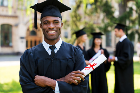 college life: Happy graduate. Happy African man in graduation gowns holding diploma and smiling while his friends standing in the background  Stock Photo