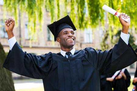 birrete de graduacion: Finalmente me he graduado! Hombre africano joven feliz en vestidos de graduaci�n que sostienen el diploma y el aumento de los brazos hacia arriba, mientras que sus amigos de pie en el fondo