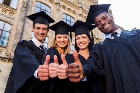 convivencia escolar: Confiados en su futuro éxito. Bajo el ángulo de cuatro graduados universitarios en vestidos de graduación de pie cerca uno del otro y mostrando sus pulgares hacia arriba Foto de archivo