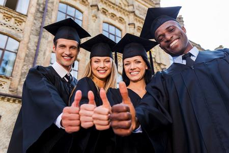 Confident in their successful future. Low angle view of four college graduates in graduation gowns standing close to each other and showing their thumbs up Stock Photo
