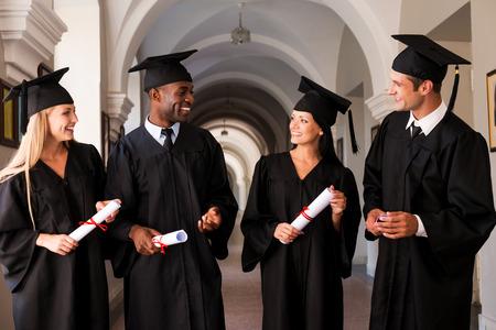 graduacion de universidad: Hablando de futuro brillante. Cuatro graduados universitarios en vestidos de graduaci�n caminando por pasillo de la universidad y hablar