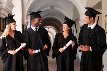Talking about bright future. Four college graduates in graduation gowns walking along university corridor and talking photo