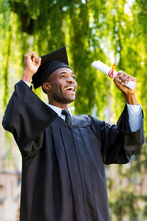 birrete de graduacion: Finalmente se gradu�! Hombre africano joven feliz en vestidos de graduaci�n que sostiene el diploma y el aumento de los brazos Foto de archivo