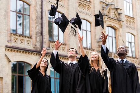 Finalmente estamos graduamos! Cuatro graduados universitarios felices en vestidos de graduación que lanzan sus juntas de mortero y sonriendo mientras está de pie cerca de la universidad