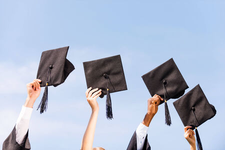 graduation gown: Finally graduated! Close-up of four hands holding mortar boards against sky background  Stock Photo