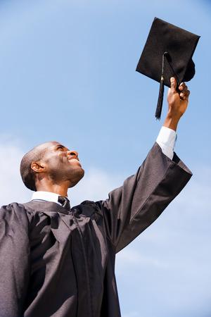 birrete de graduacion: Feliz de graduar. �ngulo de visi�n baja del hombre africano joven feliz en traje de graduaci�n celebraci�n de su junta de mortero contra el cielo azul Foto de archivo