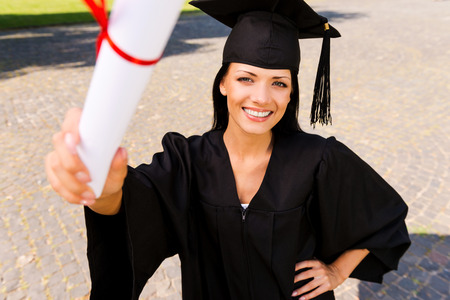 Happy graduate with diploma. Top view of happy young woman in graduation gown showing her diploma and smiling photo
