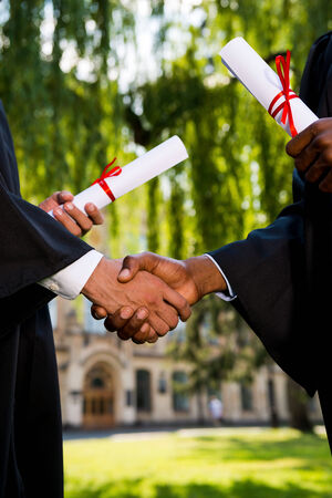 congratulating: Congratulating with graduation. Close-up of two men in graduation gowns holding diplomas and shaking hands  Stock Photo