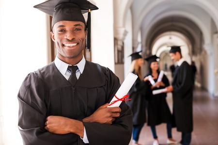 toga graduacion: Graduado Confiado. Hombre africano feliz en vestidos de graduación celebración diploma y sonriendo mientras sus amigos de pie en el fondo