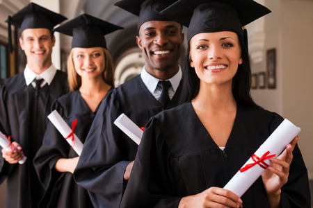college life: Ready to success. Four college graduates standing in a row and smiling