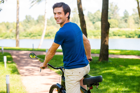 looking over shoulder: Enjoying great time in park. Rear view of happy young man riding bicycle in park and looking over shoulder