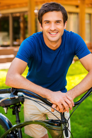 one person only: Me and my bike. Handsome young man leaning at bicycle in and smiling while standing outdoors and against house