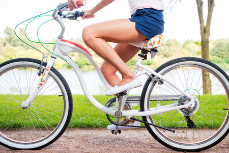 Park ride. Close-up side view of young woman riding bicycle in park Imagens