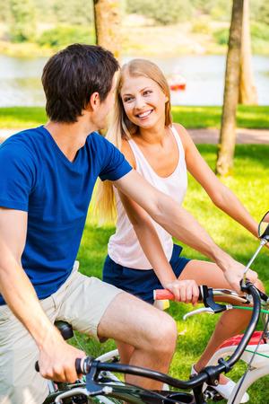 jovenes enamorados: Nos encanta pasar tiempo juntos! Hermosa joven sonriente pareja montando sus bicicletas en el parque juntos y mirando el uno al otro Foto de archivo