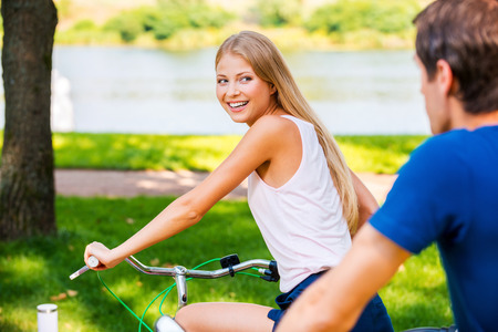 I am wining! Beautiful young smiling woman riding her bicycle and looking over shoulder while her boyfriend riding behind her photo