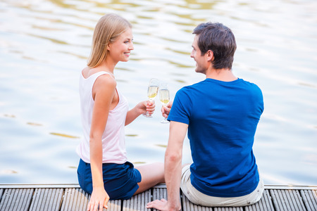 Cheers! Beautiful young loving couple sitting at the quayside together and drinking Champaign photo
