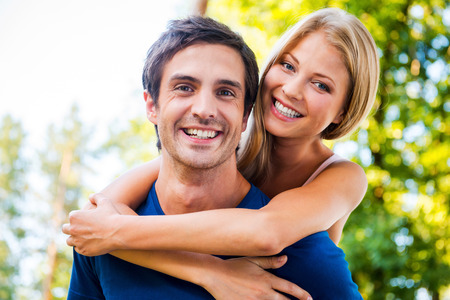 Happy to be together. Low angle view of beautiful young loving couple standing outdoors together while woman hugging her boyfriend and smiling Banco de Imagens