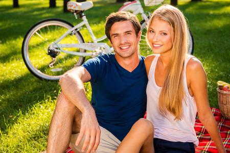 picnic blanket: Un buen d�a para la comida campestre. Feliz pareja de j�venes amantes de relax en el parque juntos, mientras que sentado en una manta de picnic y sonriente, mientras que la bicicleta de pie en el fondo