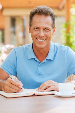 i pad: I love working outdoors. Confident mature man writing something in his note pad and smiling while sitting at the table outdoors with house in the background  Stock Photo