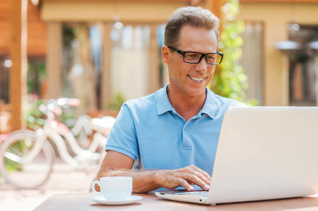 Man working outdoors. Cheerful mature man working at laptop and smiling while sitting at the table outdoors with house in the background