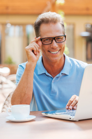 adjusting: Working with pleasure. Cheerful mature man working at laptop and smiling while sitting at the table outdoors with house in the background