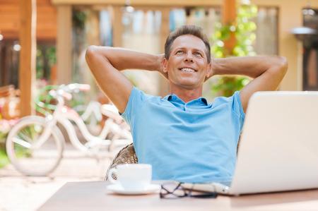 relajado: Feliz d�a so�ador. Hombre maduro Relaxed la mano detr�s de la cabeza y sonriendo mientras est� sentado en la mesa al aire libre con el ordenador port�til en �l Foto de archivo