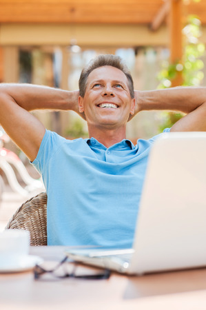 Dreaming of vacation. Relaxed mature man holding hands behind head and smiling while sitting at the table outdoors with laptop on it  photo