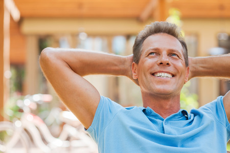 man behind: Happy day dreamer. Relaxed mature man holding hands behind head and smiling while outdoors with house in the background