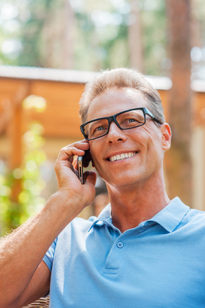 Sharing good news with friends. Happy mature man talking on the mobile phone and smiling while sitting outdoors with house in the background  photo