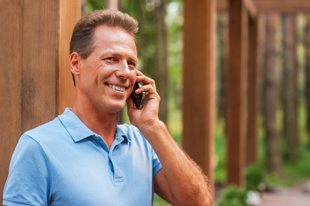 Good talk. Happy mature man talking on the mobile phone and smiling while standing outdoors  photo