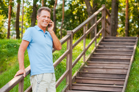 Good talk with friend. Cheerful mature man talking on the mobile phone and smiling while standing at wooden staircase   photo
