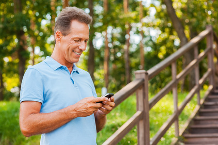 Examining his brand new smart phone. Cheerful mature man holding mobile phone and looking at it with smile while standing at wooden staircase