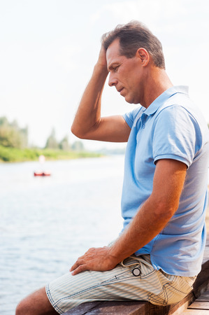 man looking down: Worried and depressed man. Side view of depressed mature man touching head with hand and looking down while sitting at the quayside  Stock Photo