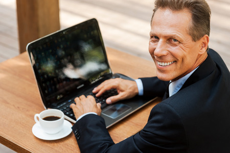 I love working outdoors. Top view of cheerful mature man in formalwear working on laptop and smiling while sitting in outdoors cafe