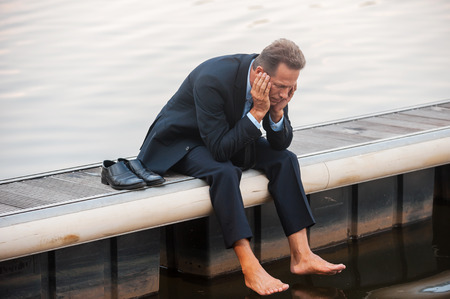 Depressed businessman. Depressed mature businessman holding head in hands while sitting barefoot at the quayside